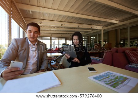 Male and female architects debating finding solution of problem with graphic sharing different ideas and opinions working in coffee shop  using modern technologies to fulfill project in time
