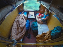 Male and female backpackers resting while travelling in a cool sleeper train. Man lies in bed while his girlfriend is sitting and looking through the window during a train journey across Vietnam.