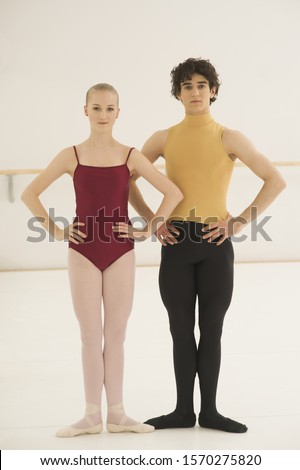 Male and female ballet dancers standing together in first position
