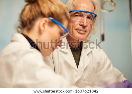 male and female chemists analysing a new drug in a forensic laboratory. Very focused at work in a bright lab. Talking.