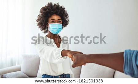 Male and female colleagues fist bumping, group of young people with protective face masks. New normal greeting with fist bump. Two people wearing protective face mask and greeting with fist bump