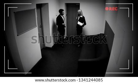 Photo of  Male and female colleagues talking office corridor, CCTV camera effect, footage