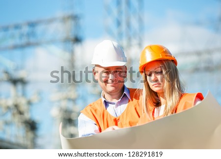 male and female construction workers in the helmet against electrical designs