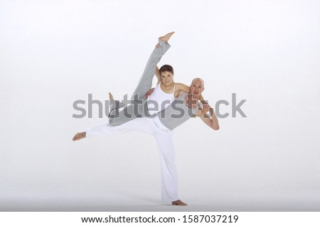 Male and female dancers in harmony, legs raised