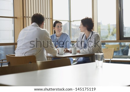 Male and female doctors communicating with nurse on work break in cafeteria