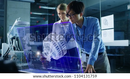 Male and Female Engineers Have Discussion while Using Modern Computer With Transparent Holographic Display. Monitor Shows Mechanical Gear Detail Visualization. Shot in Modern Office.