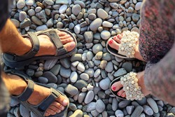 Male and female feet of lovers in sandals across from each other on pebble surface, top view