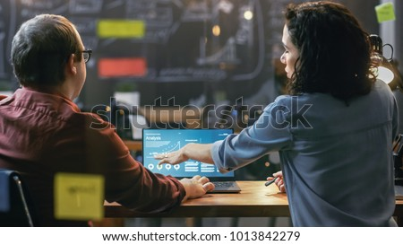 Male and Female Financiers Look at Statistics and Graphs Shown on the Laptop, They Talk Solving Problems. In the Background Creative Office.