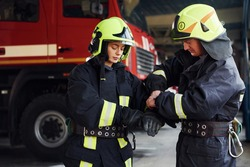 Male and female firefighters in protective uniform standing together.