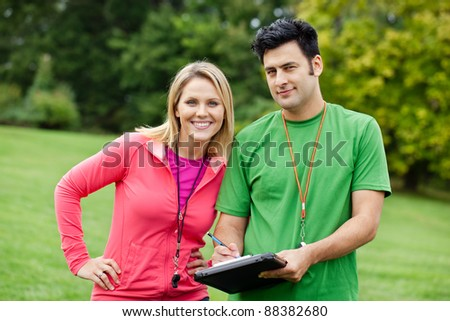Male and female fitness trainers holding a clipboard