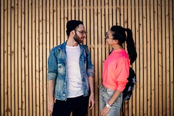 Male and female friends dressed in fashionable streetwear standing near promotional background with copy space for brandname and communicating, trendy hipster guys talking at wooden publicity area