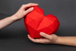 Male and female hand holding a red heart shaped polygonal paper on a gray background. Red polygonal paper heart for Valentine's Day or any other love invitations. Holiday and medicine concept.