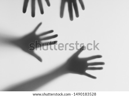 Male and female hands behind a frosted glass. Silhouettes of male and female hands. Conceptual scene.