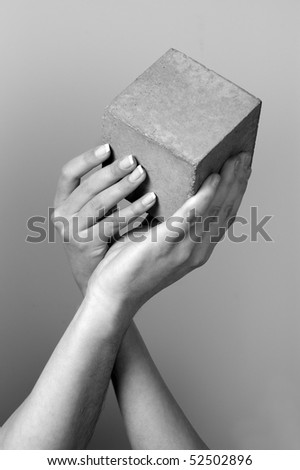 male and female hands hold concrete cube