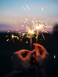 Male and female hands holding sparkling fireworks to the sky at twilight against sunset sky