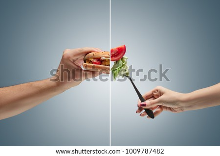Male and female hands holding tasty hamburger and fresh vegetables on a blue background. concept of confrontation, differences in taste and preference. concept of healthy and unhealthy food