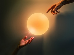 Male and female hands pointing to glowing light sphere over dark wall background. Creation holiday idea concept.