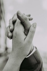 Male and female hands reach out to each other and touch the sky with their fingers. Lovers' hands intertwined