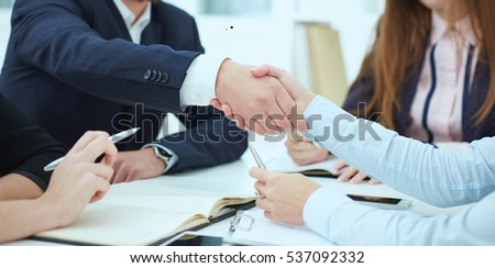 Male and female handshake in office. Serious business and partnership concept. Partners made deal, sealed with handclasp. #537092332