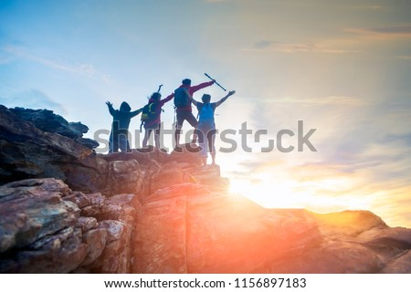 Male and female hikers climbing up  mountain cliff . helps and team work concept.
