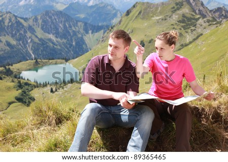 Male and female hikers in the German Alps near Oberstdorf reading a map for orientation.