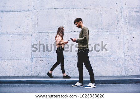 Male and female hipsters walking on grey wall background ignoring each other preferring social networks,students chatting online instead of communicating in real life strolling pon publicity area