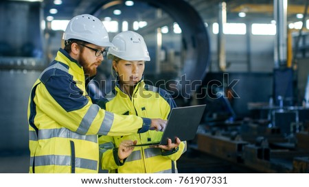 Male and Female Industrial Engineers in Hard Hats Discuss New Project while Using Laptop. They Make Showing Gestures.They Work in a Heavy Industry Manufacturing Factory. Stockfoto ©