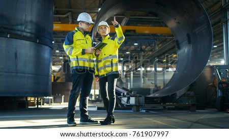 Male and Female Industrial Engineers in Hard Hats Discuss New Project while Using Tablet Computer. They're Making Calculated Engineering Decisions.They Work at the Heavy Industry Factory.