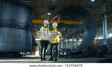 Male and Female Industrial Engineers Look at Project Blueprints While Standing Surround By Pipeline Parts in the Middle of Enormous Heavy Industry Manufacturing Factory