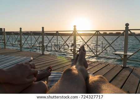 Male and female legs lie on a lounger on the pier at sunset. #724327717