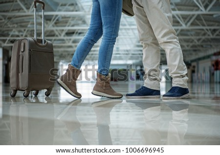 Male and female legs standing close to each other. Luggage is near them. Close up - Shutterstock ID 1006696945