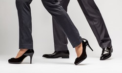 Male and female legs walking on grey background
