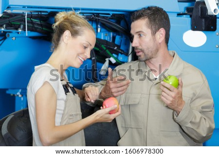 male and female manual workers eating apple for lunch