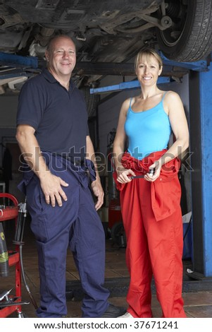 Male and female mechanics working on car