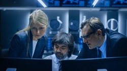 Male and Female Operators Working On Computers in System Control Room. Secret Government Agency Analysts Doing Research, Conducting Cyber Security Investigation.