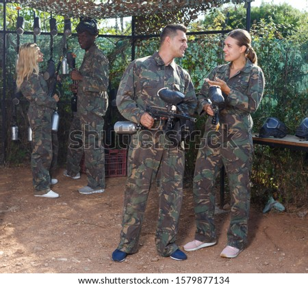 Male and female paintball players getting ready for match outdoors