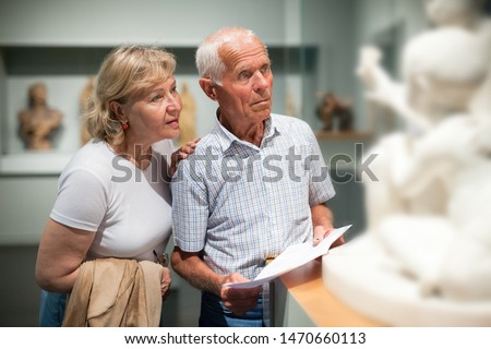 Male and female pensioners visiting exposition of museum and reading guidebook Сток-фото ©
