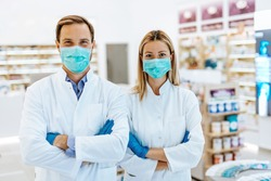 Male and female pharmacists with protective mask on their faces working at pharmacy. Medical healthcare concept.