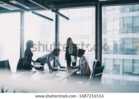 Male and female professionals teamworking during brainstorming cooperation on paper documents, group of diverse employers discussing corporate investment of firm capital briefing in conference room