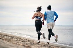 Male and female runner workingout on the beach
