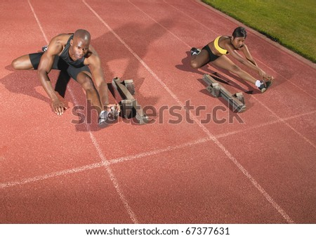 Male and female runners stretching on track