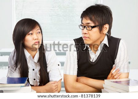 Male and female student looking each other full of hatred