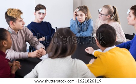 Male and female students playing guess-who game in school