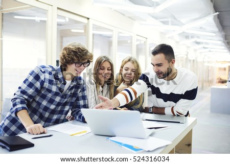 Male and female students showing their business project about accounting income of  company while coach is pointing on successful concept strategy, correcting mistakes sitting in university library