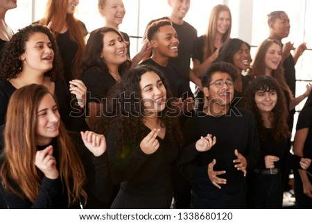 Male And Female Students Singing In Choir At Performing Arts School Stock photo ©