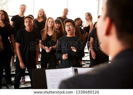 Male And Female Students Singing In Choir With Teacher At Performing Arts School Stock photo ©