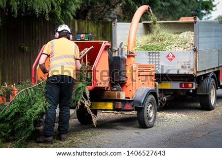 Male Arborist using a working wood chipper machine.The tree surgeon is wearing a safety helmet with a visor and ear protectors. Stock photo ©