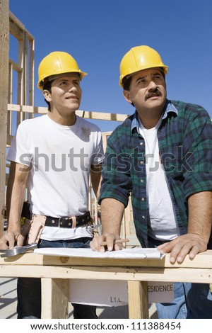 Male architects with blueprint at a construction site