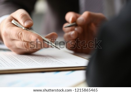 Male arm in suit and tie fill form clipped pad with silver pen closeup. Sign gesture read pact sale agent bank job make note loan credit mortgage investment finance executive chief legal teamwork law #1215865465