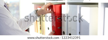 Male arms pick red file folder from office book shelf closeup. Store pile of project documentation concept #1223412391